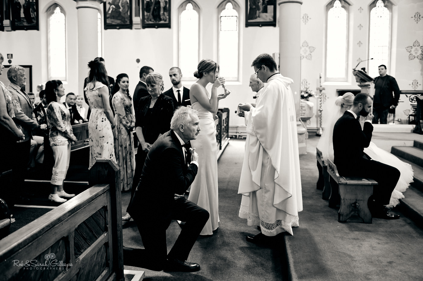 Bride and groom kiss in Catholic wedding at St Anne's church Birmingham