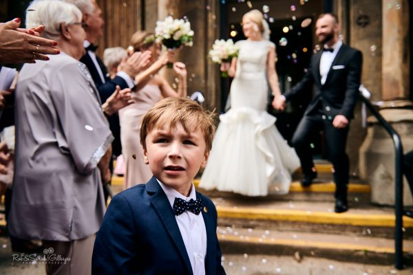 Young boy looks back as bride and groom have confetti thrown