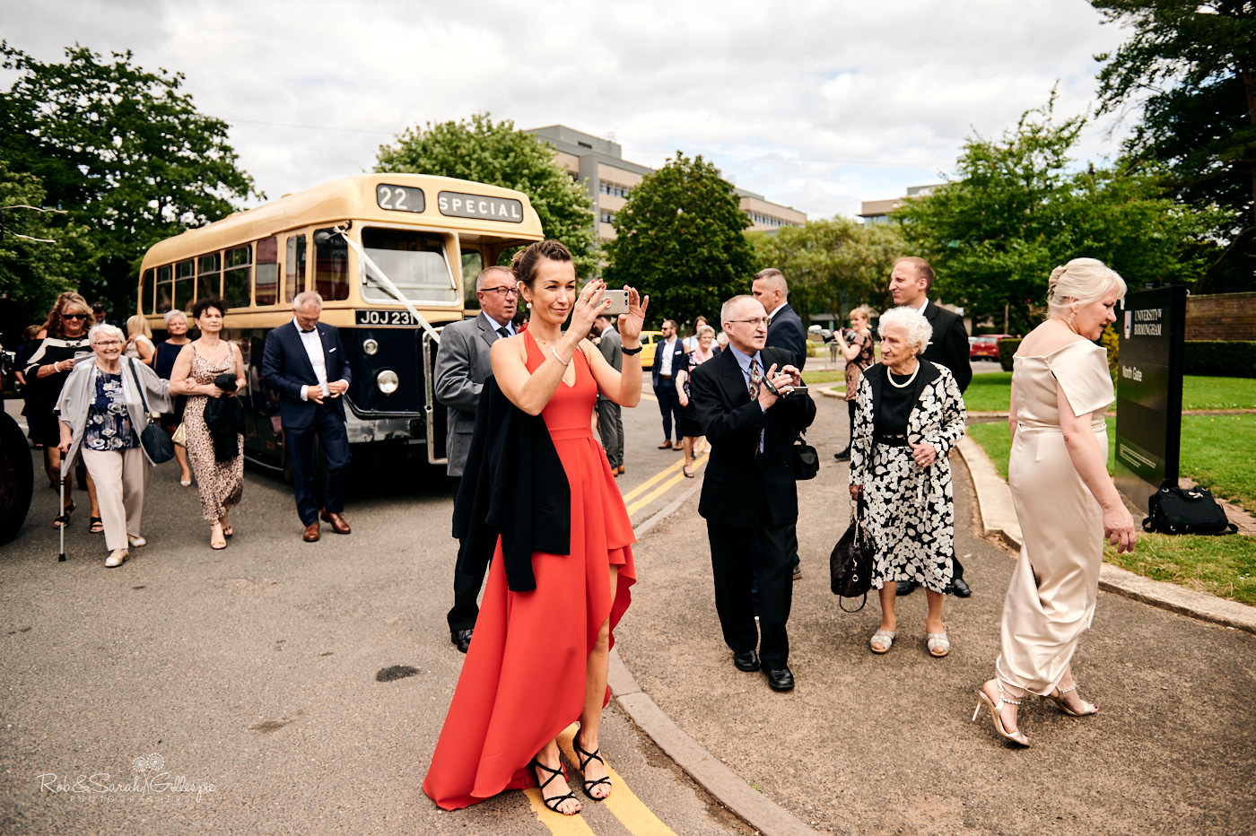 Bride, groom and wedding guests walk through Birmingham University grounds