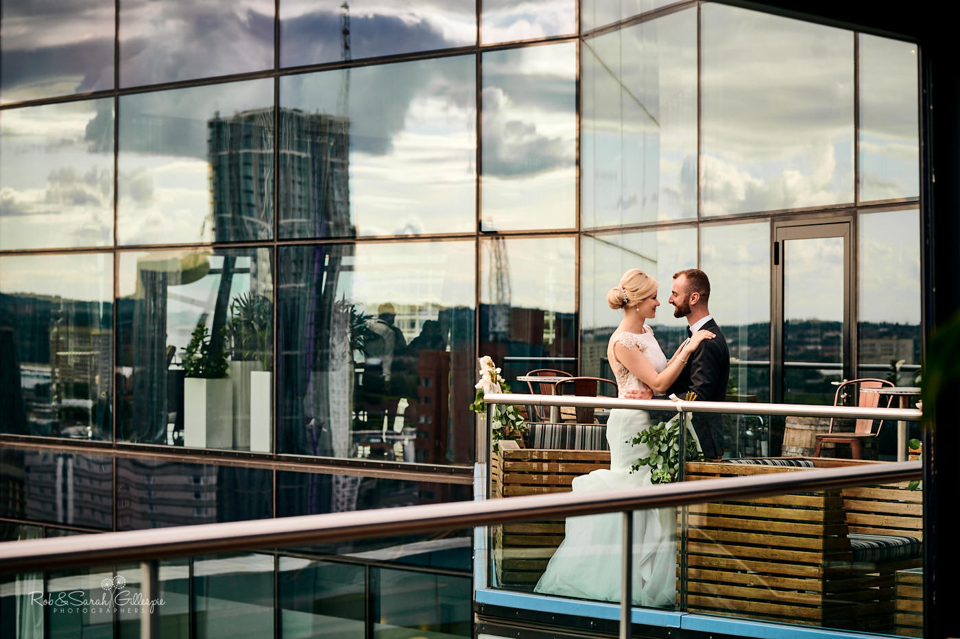 Bride and groom silhoutted in window overlooking Birmimgham at The Cube