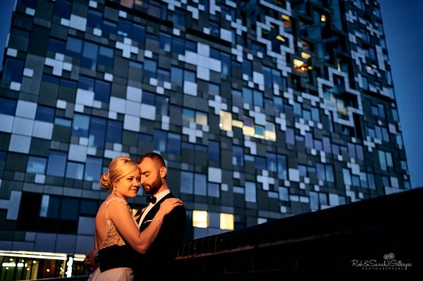Bride and groom in beautiful light with building
