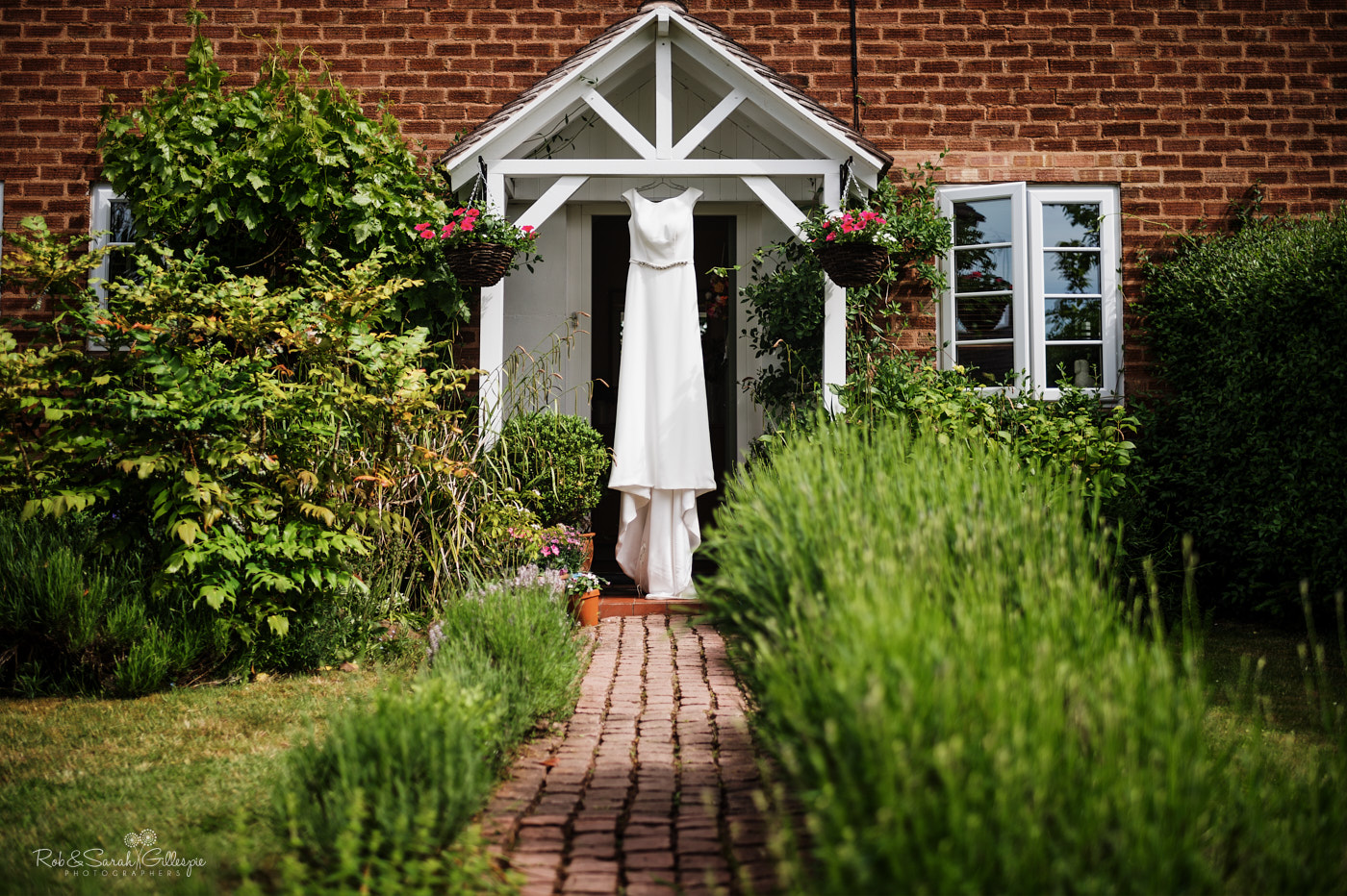 Wedding dress hanging in doorway on summers day