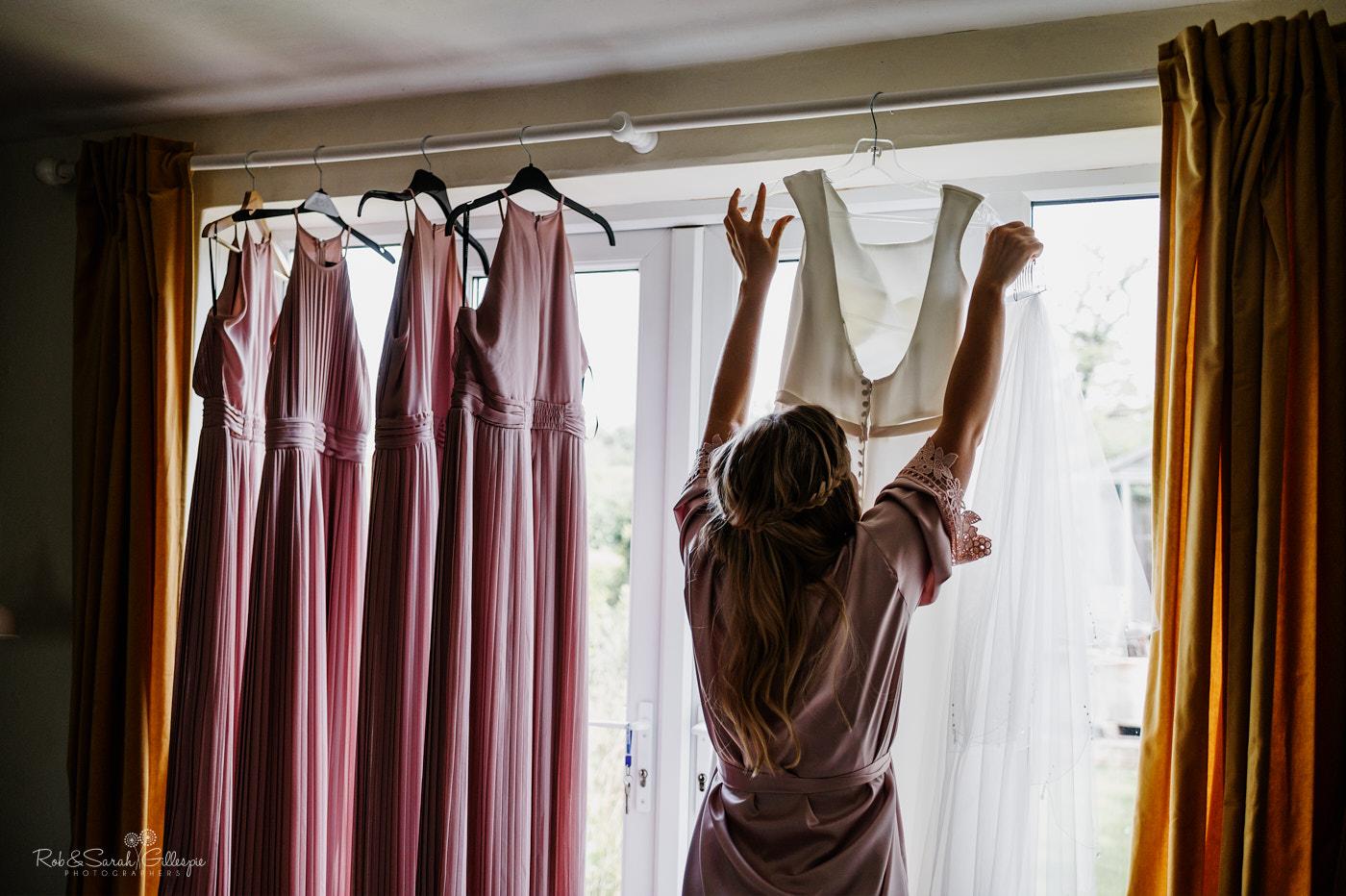 Bridesmaid adjusting wedding dress hanging in window