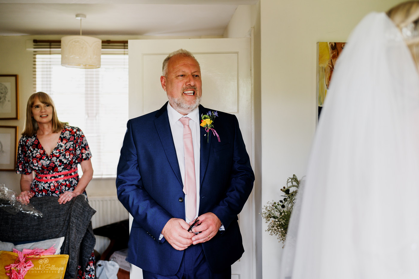 Bride's dad smiling has he sees her ready for wedding
