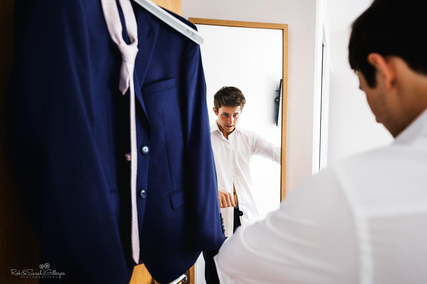 Groom looks in mirror as he prepares for wedding