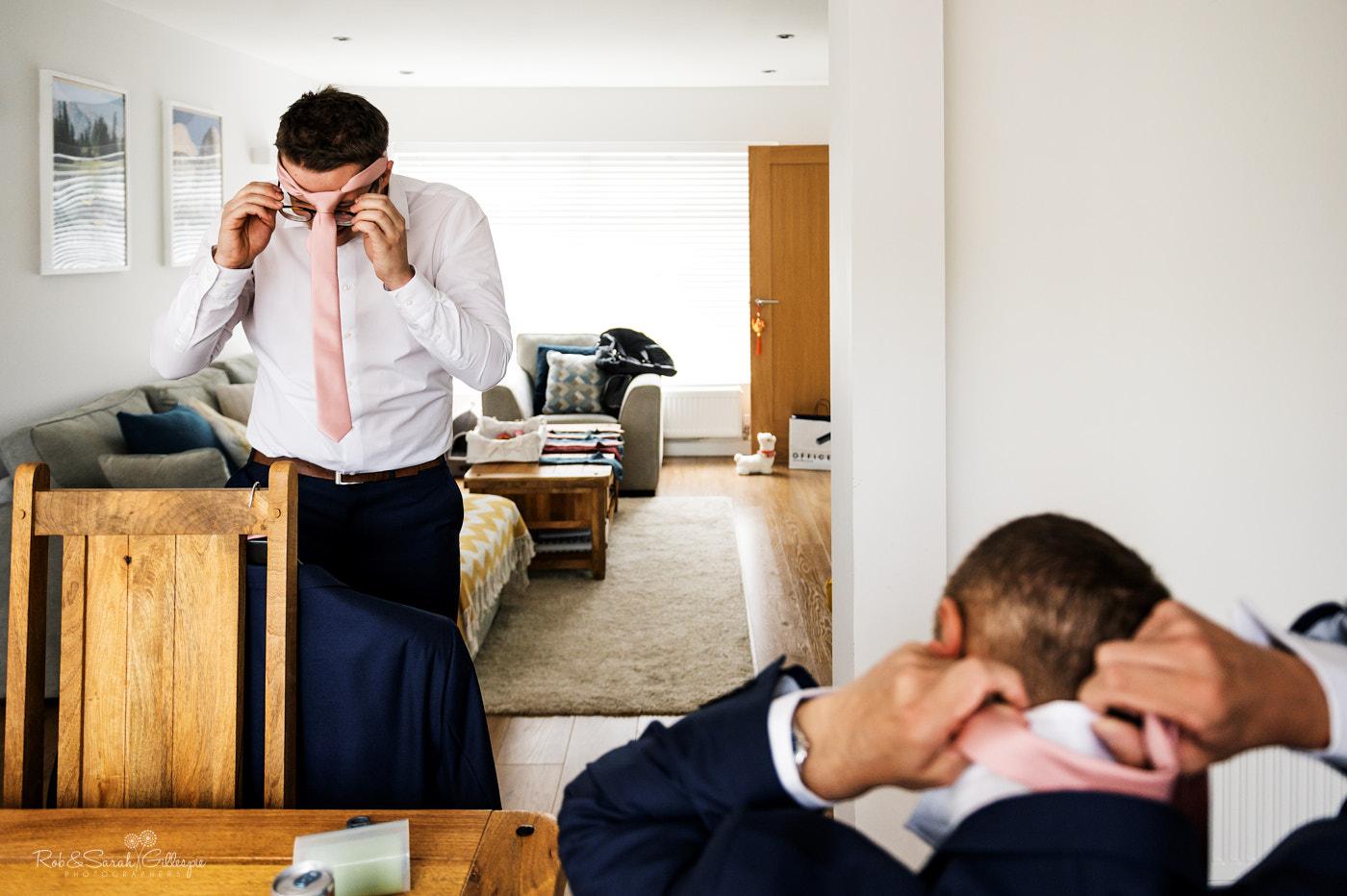 Groomsmen fix ties as they prepare for wedding