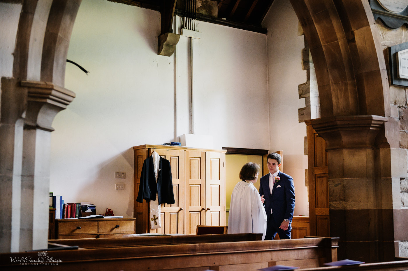 Groom talks with vicar before wedding at St Leonards church Clent