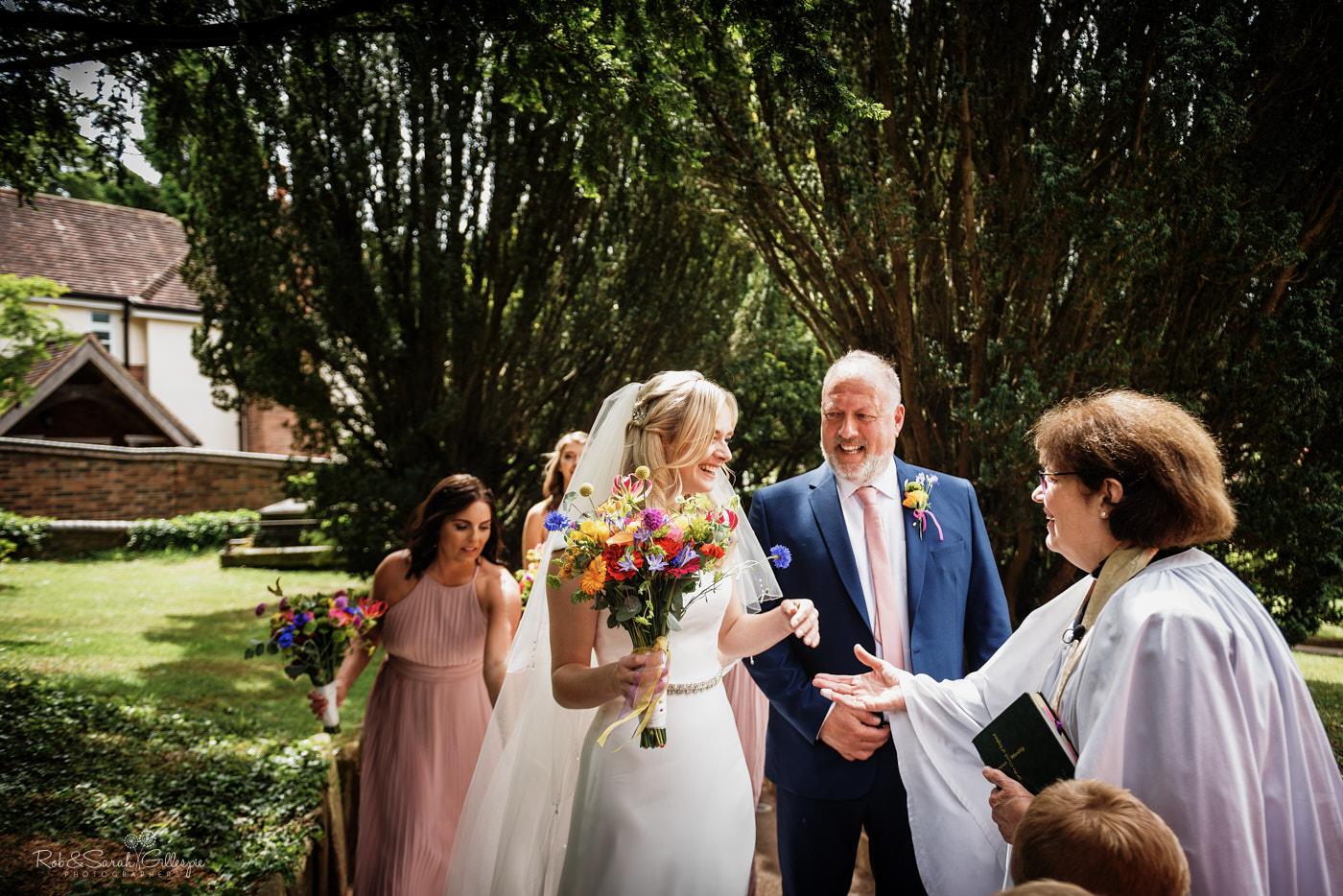 Vicar greets bride as she arrives for wedding at church