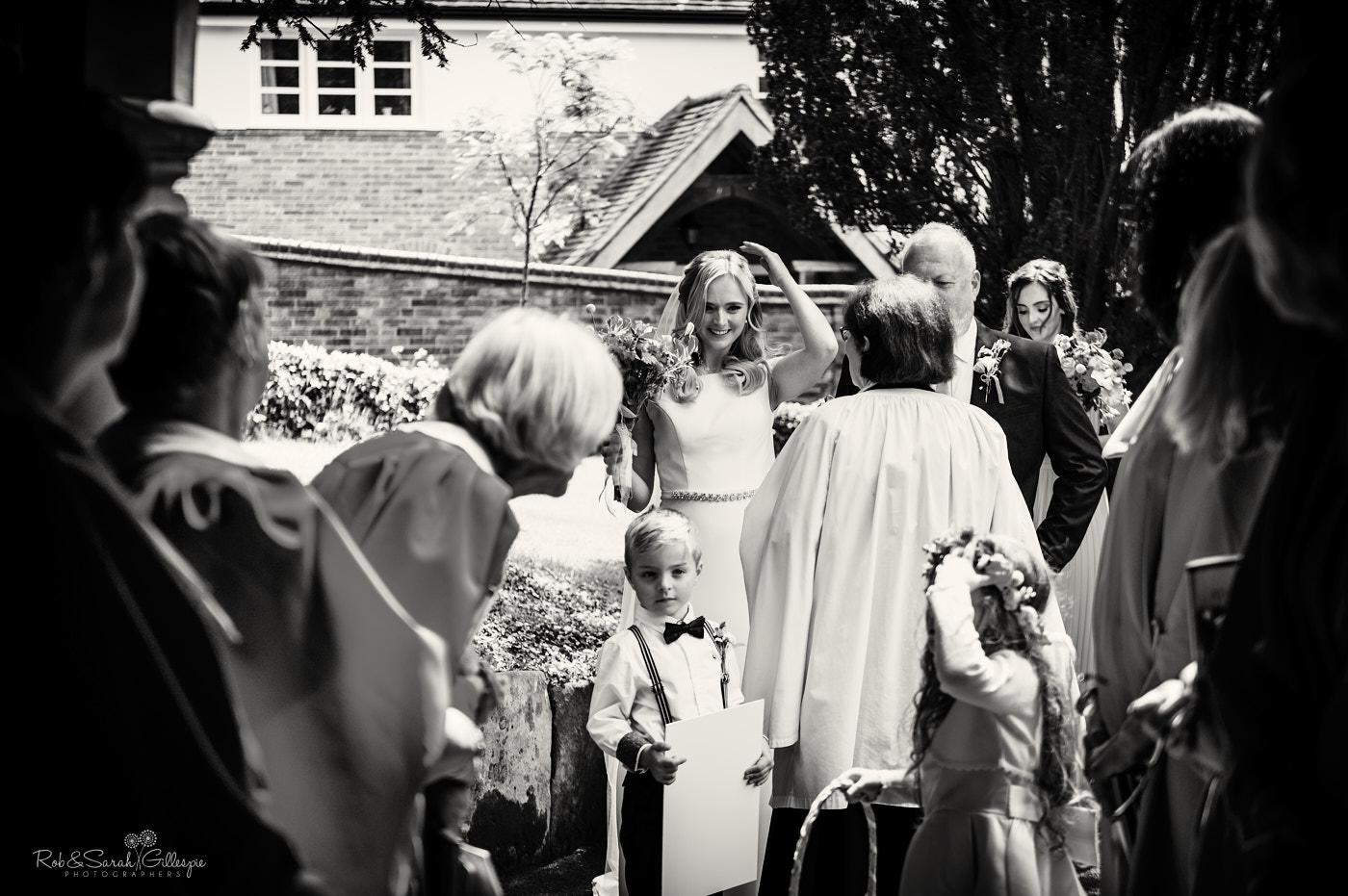 Bride and dad talk to vicar before wedding