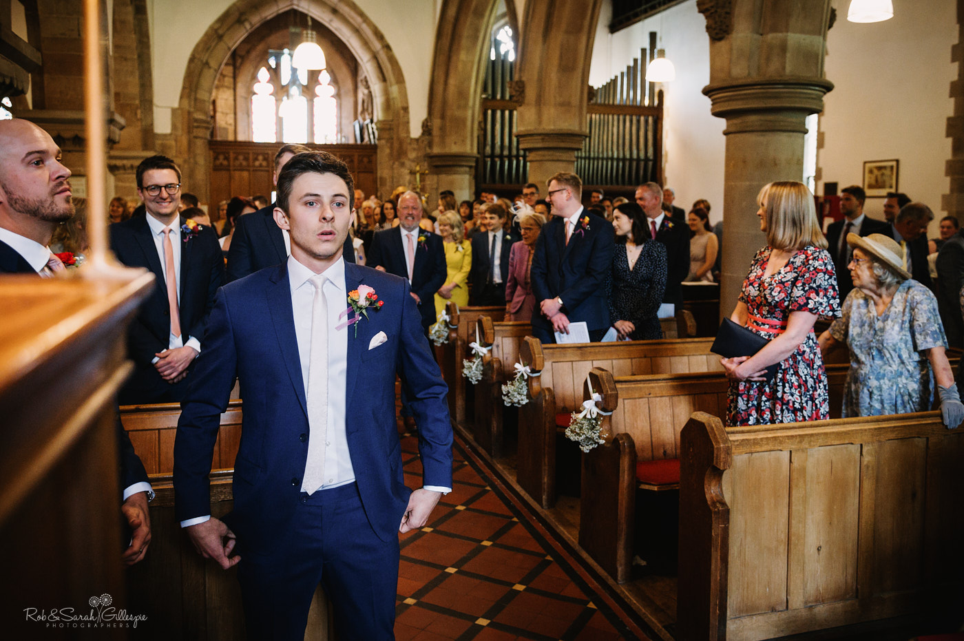 Groom waits nervously for bride at altar in church