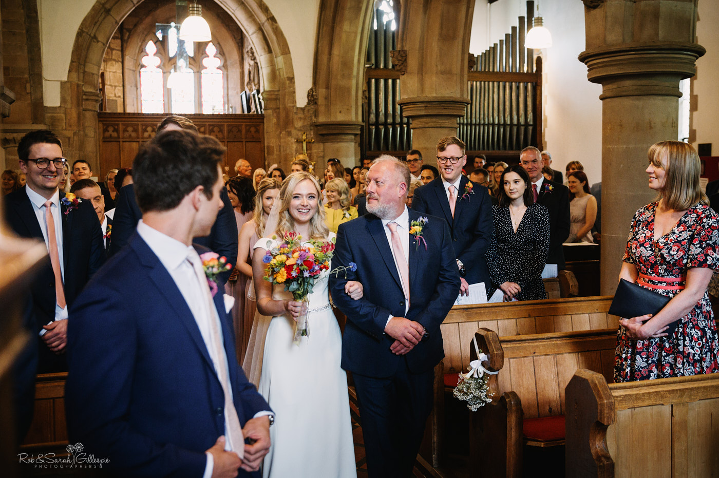 Groom turns to see bride as she walks up the aisle in church