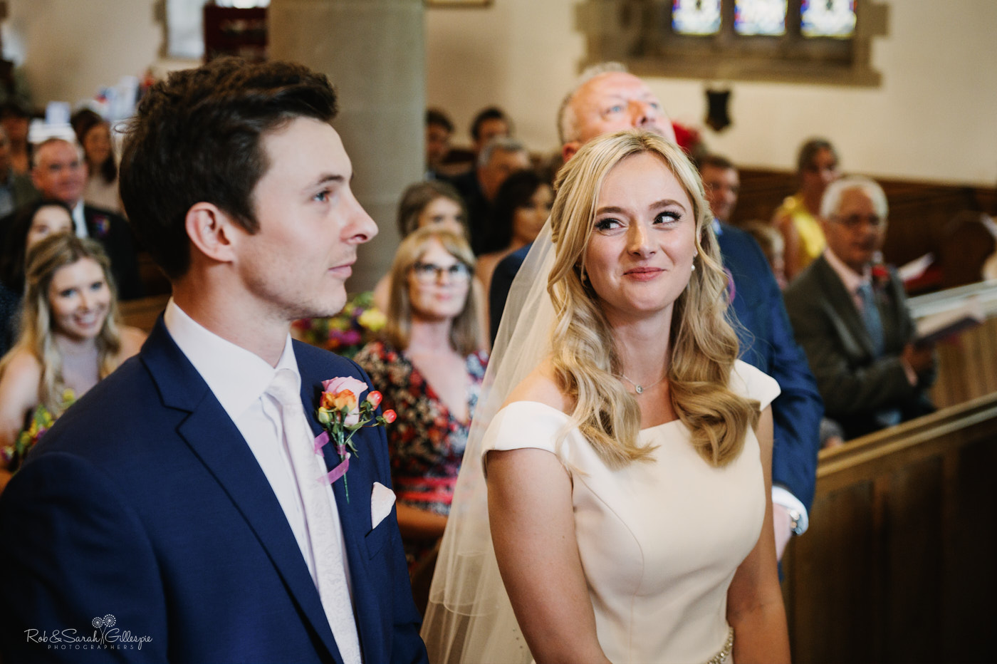 Bride smiles at groom during wedding ceremony in church