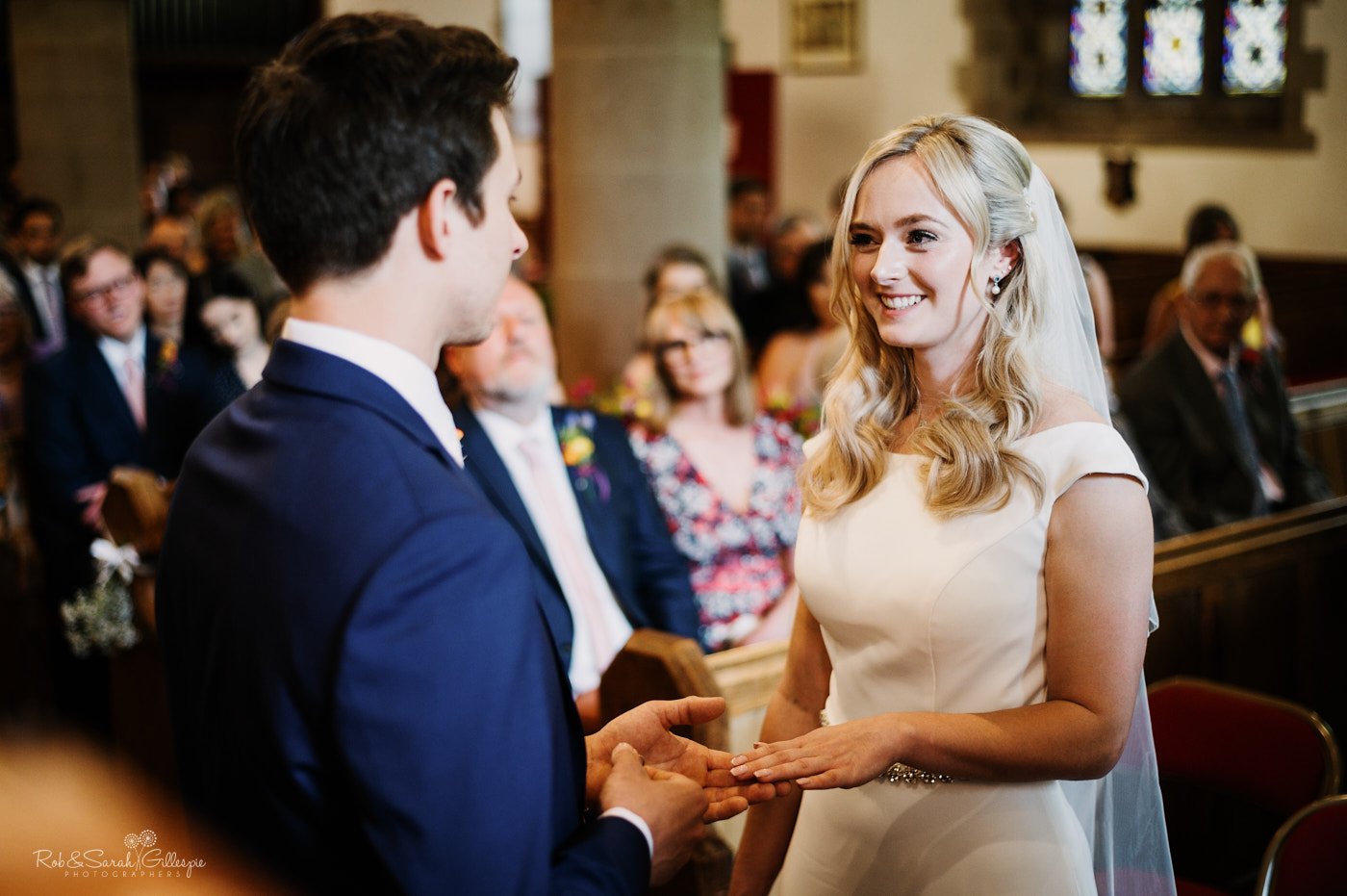 Bride and groom exchange rings during wedding ceremony in church