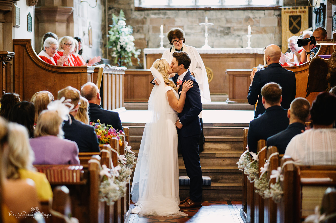 Bride and groom kiss during wedding ceremony in St Leonard's church Clent