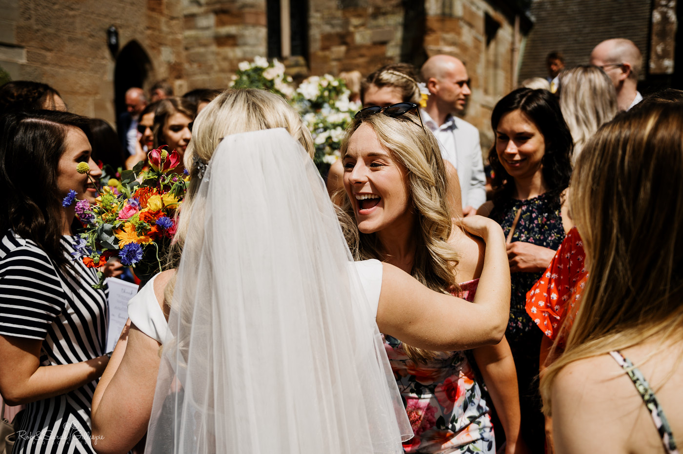 Wedding guests hug and congratulate couple at St Leonard's church in Clent