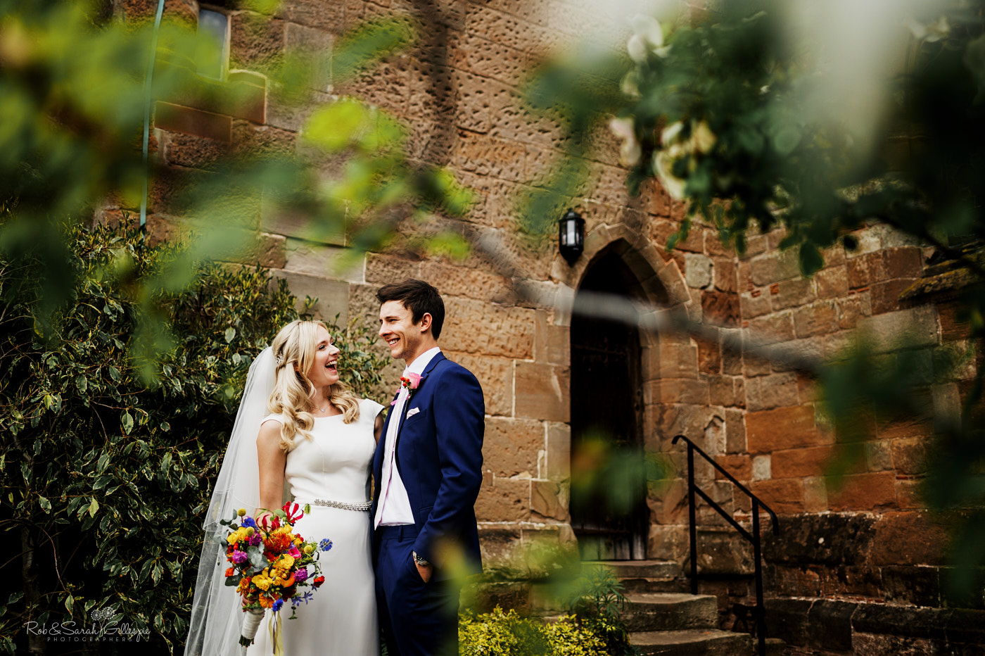 Bride and groomn laugh together after wedding at St Leonard's church Clent