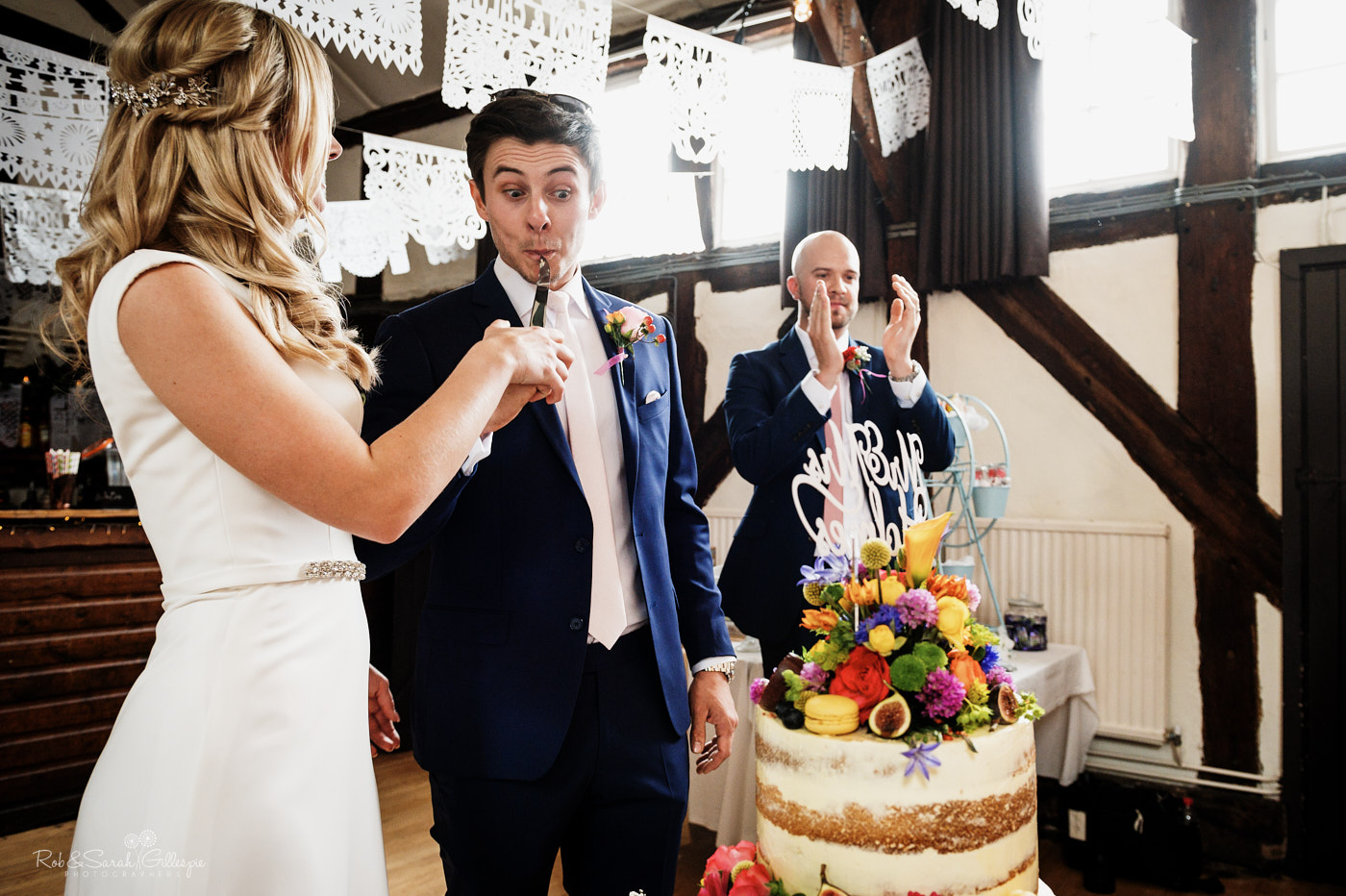 Bride and groom cut wedding cake at Belbroughton village hall
