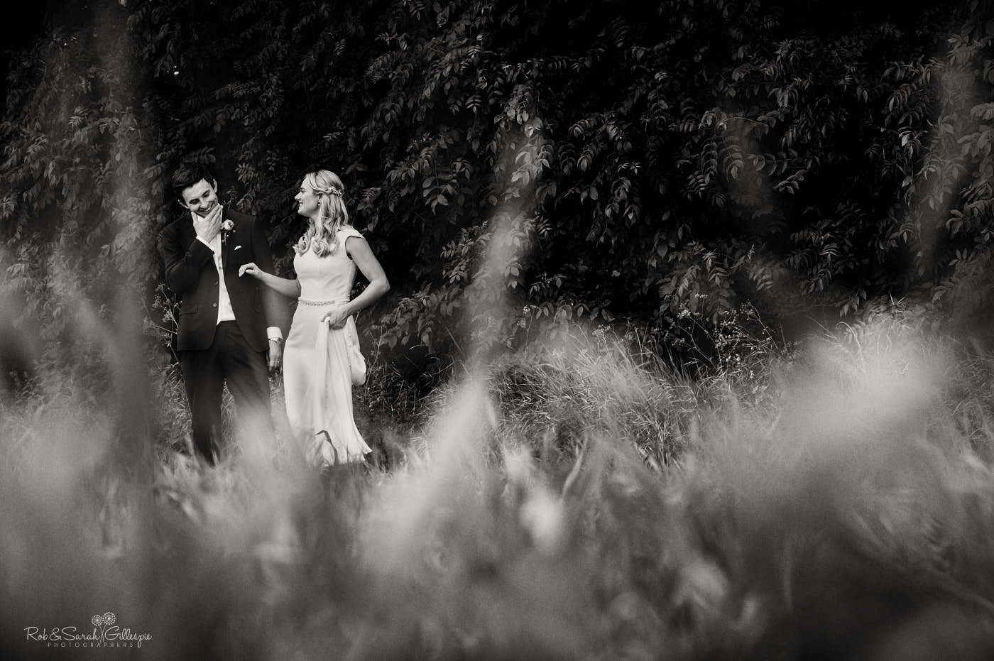 Bride and groom relax together in fields near village hall in Belbroughton