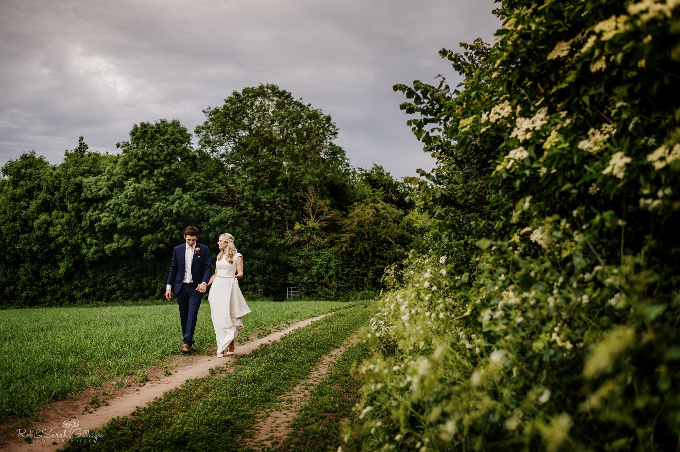 Newlyweds walk in fields near Belbroughton village hall