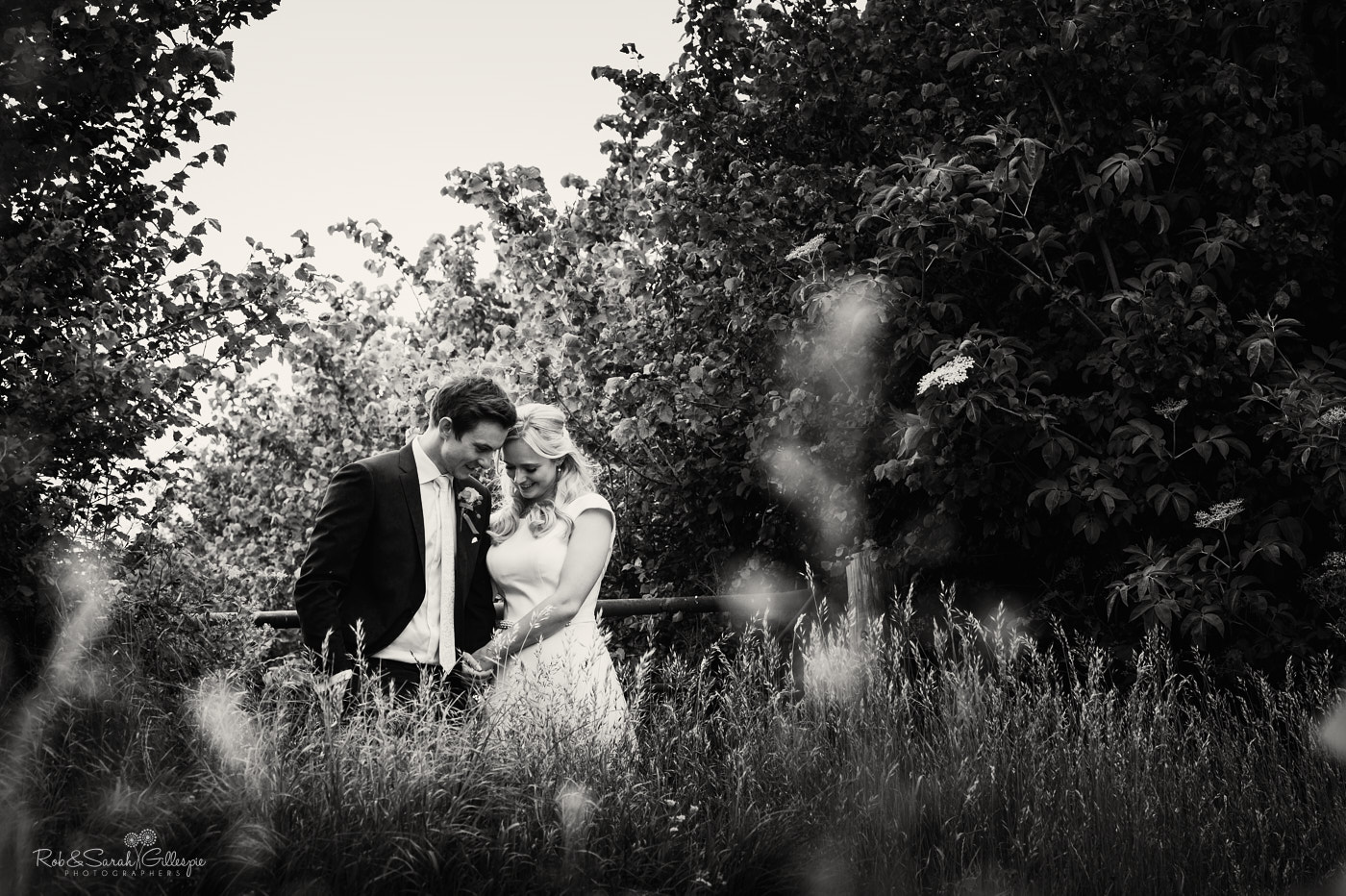 Bride and groom laughing and relaxing in fields near church hall in Belbroughton Worcestershire