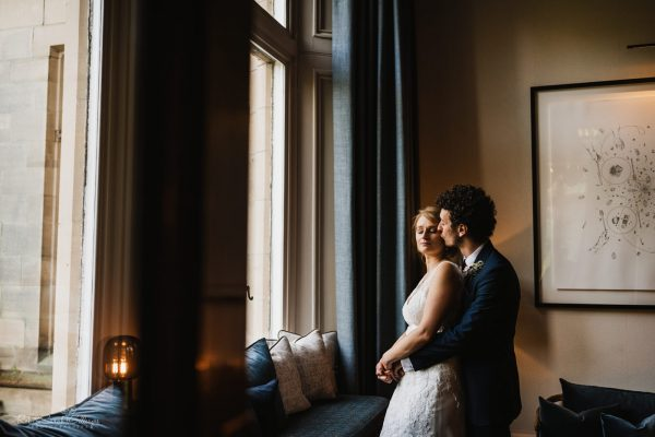 Bride and groom in window light at Hampton Manor