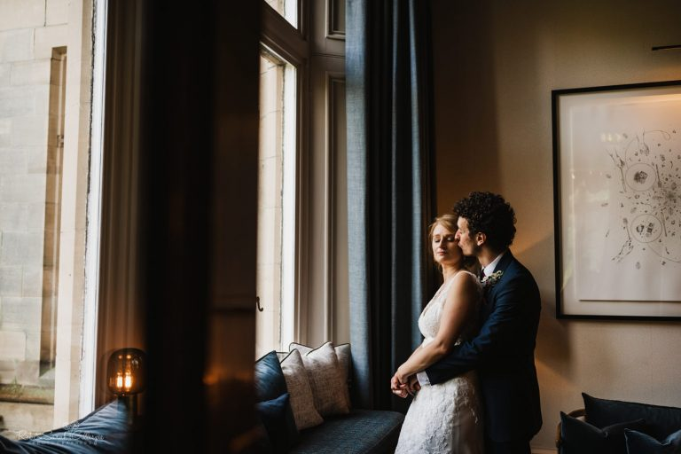 Bride and groom in window light at Hampton Manor
