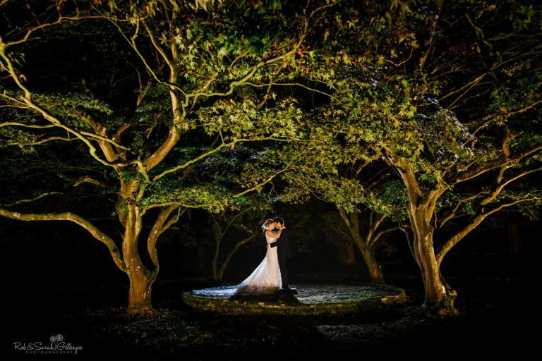 Bride and groom under trees at night at Hampton Manor