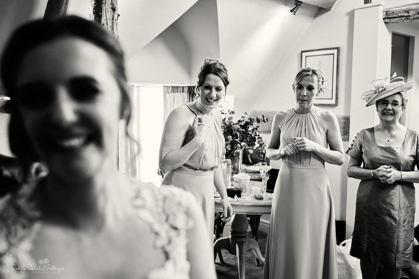 Bridesmaids watch as bride has wedding dress fastened