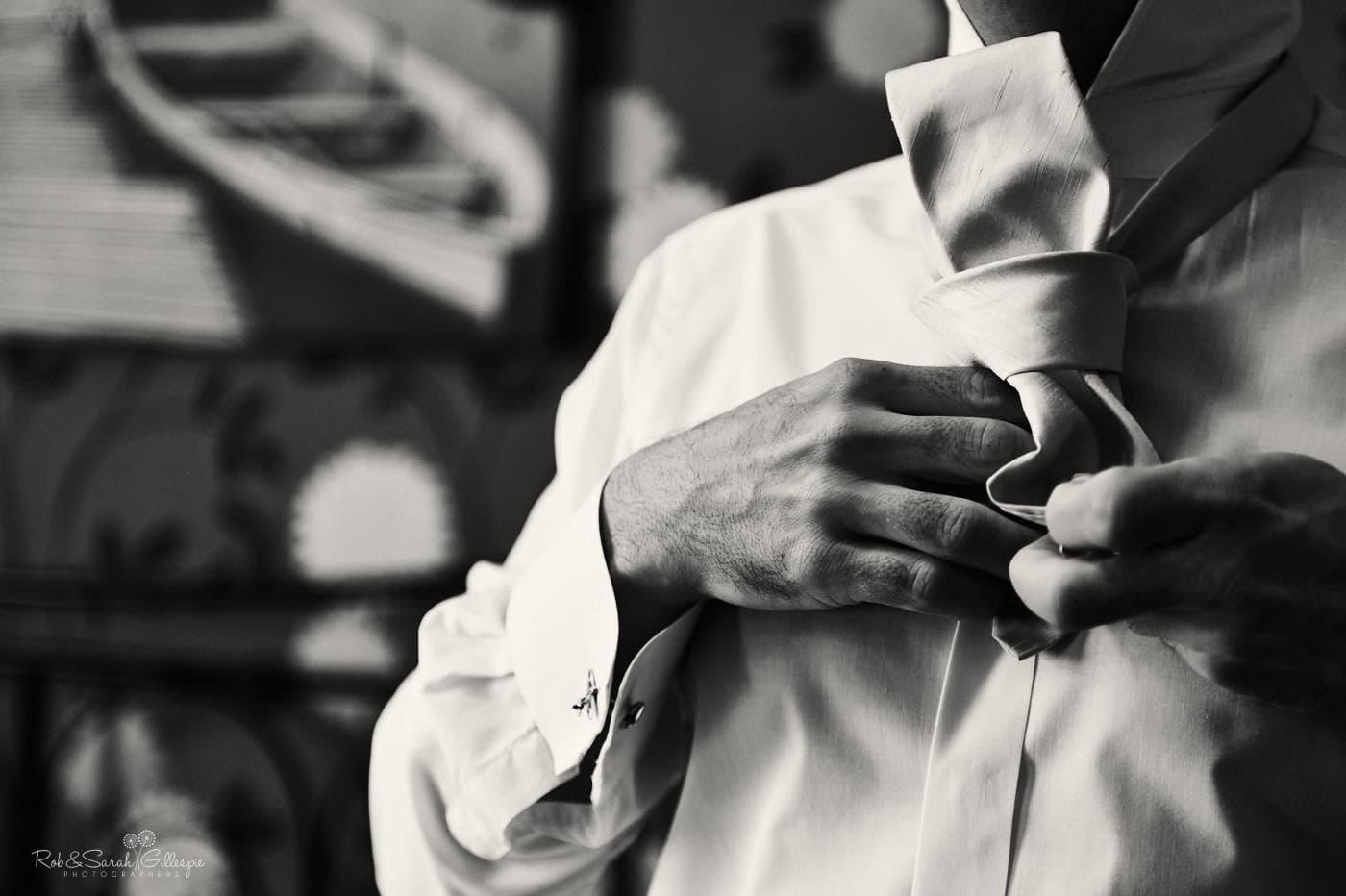 Groom fastens tie