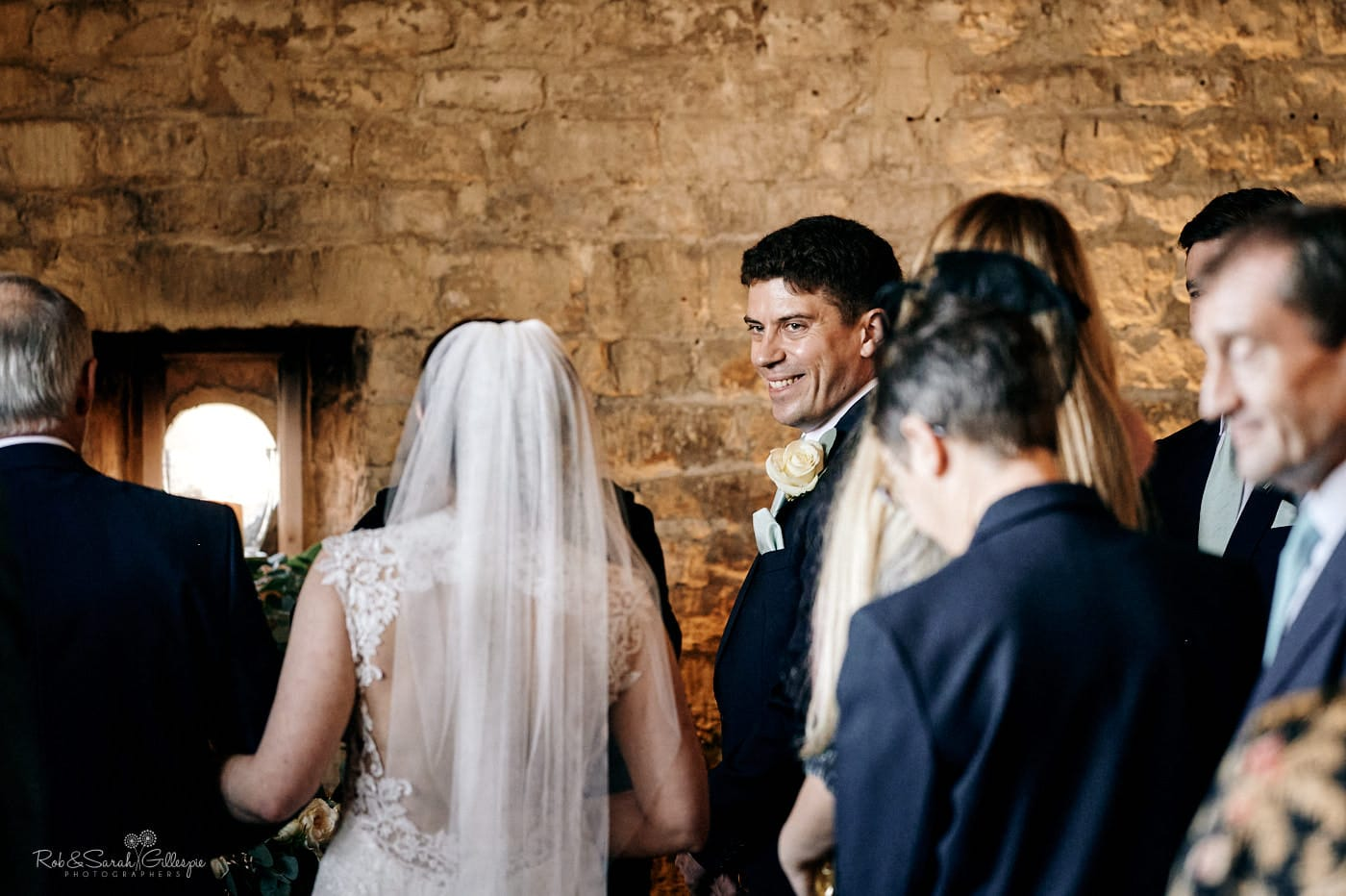 Groom smiling as he sees bride at Lapstone Barn wedding