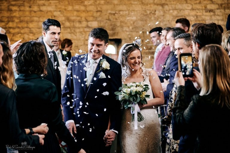 Bride and groom have confetti thrown over them as they leave wedding ceremony at Lapstone Barn