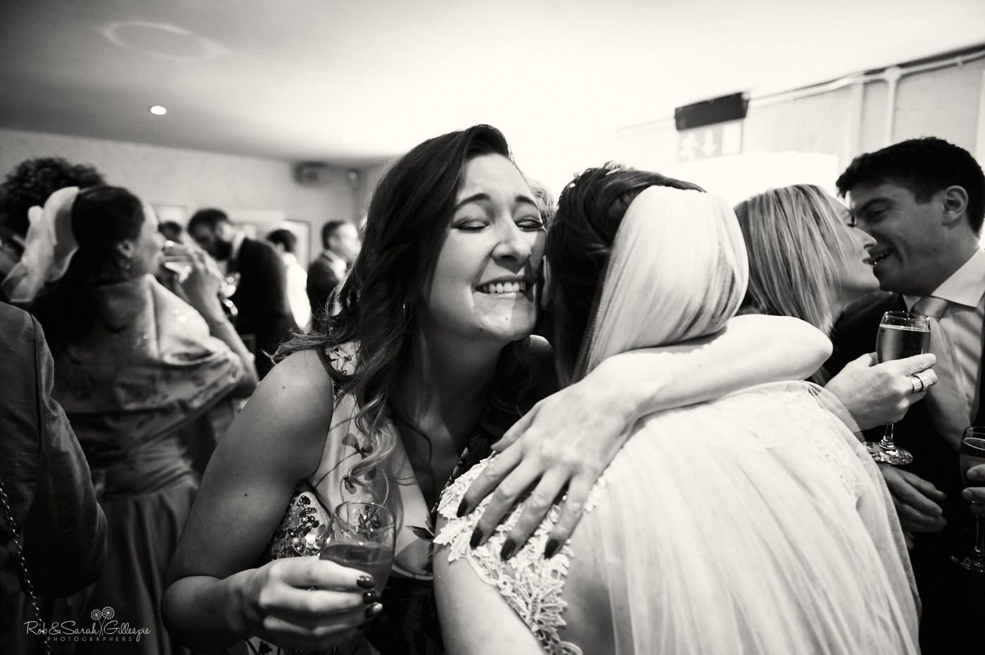 Wedding guests hugs bride at Lapstone Barn
