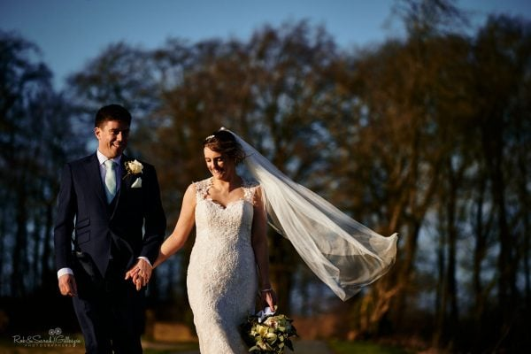 Bride & groom walking through Gloucestershire countryside