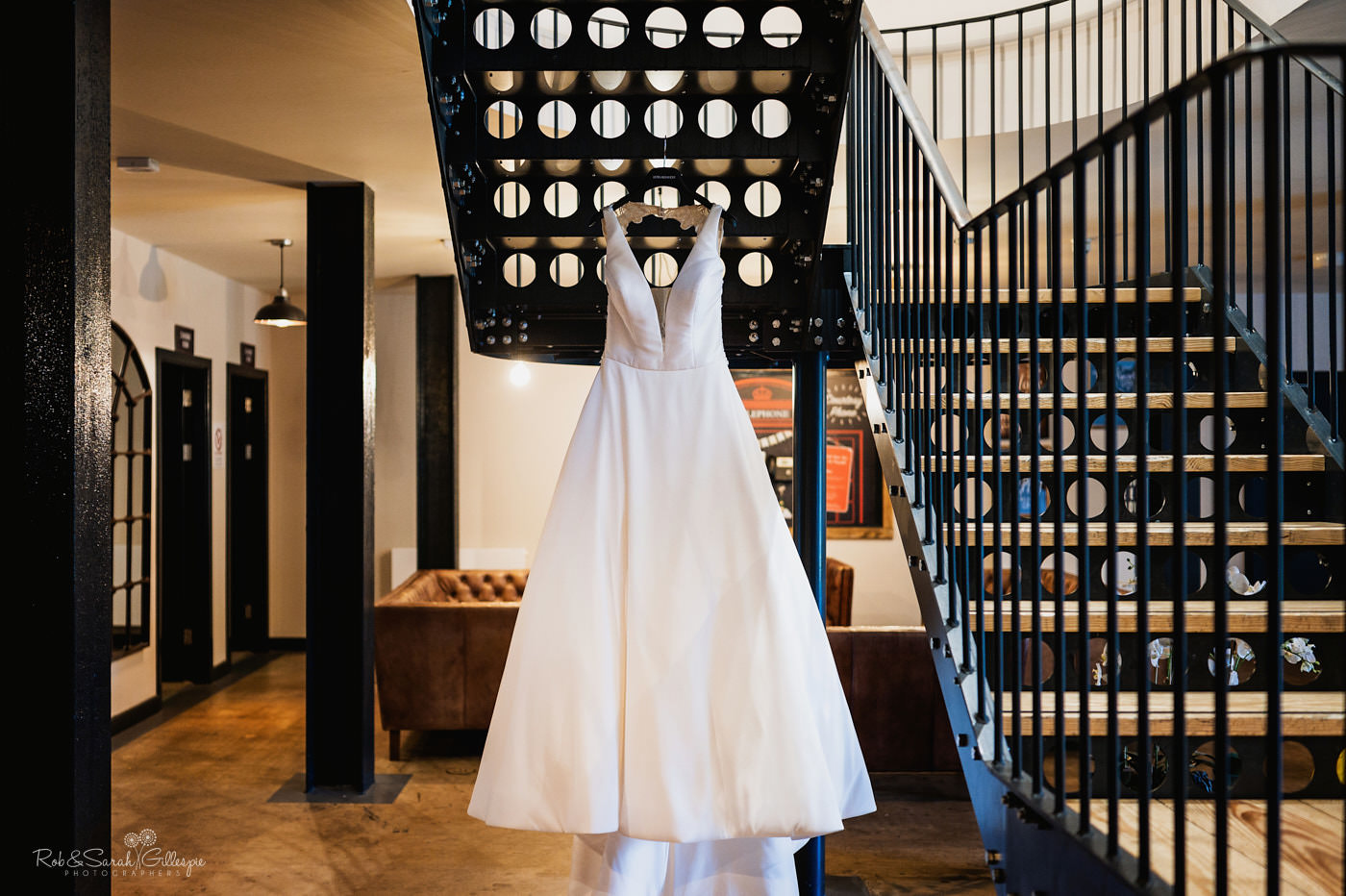 Wedding dress hanging on staircase at The Mill Barns