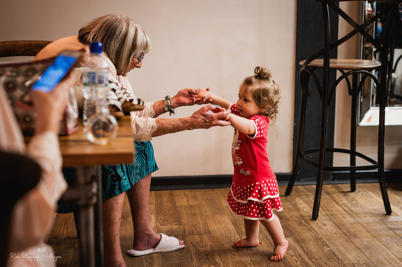 Bride's grandmother plays with toddley while getting ready for wedding