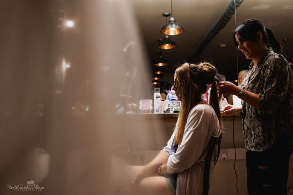 Bride has hair styled before wedding at The Mill Barns