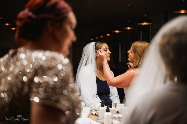 Bride has makeup applied while bridesmaid looks on