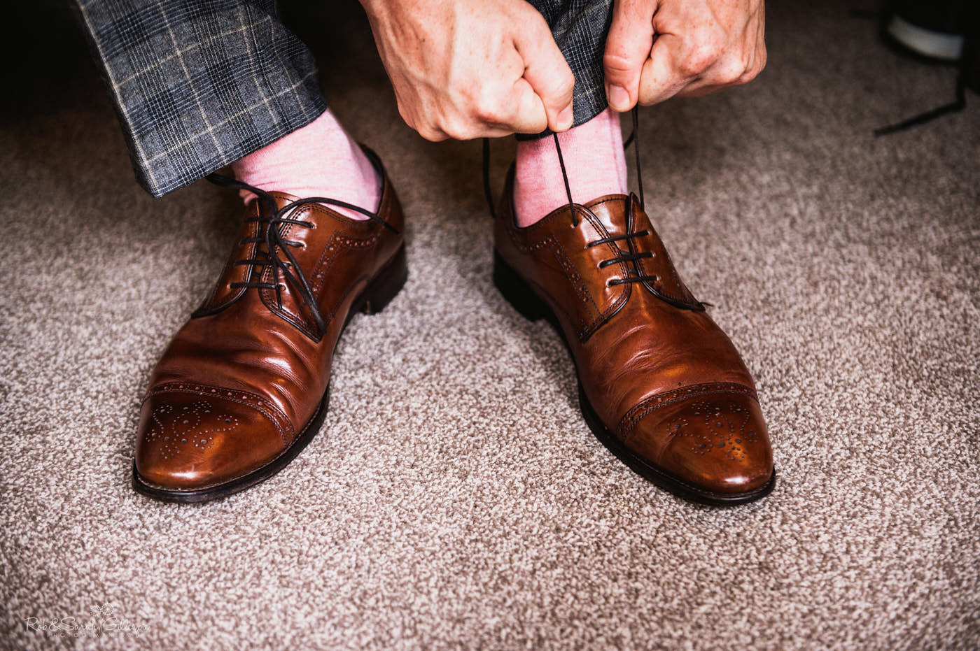 Groom ties shoelaces as he prepares for wedding