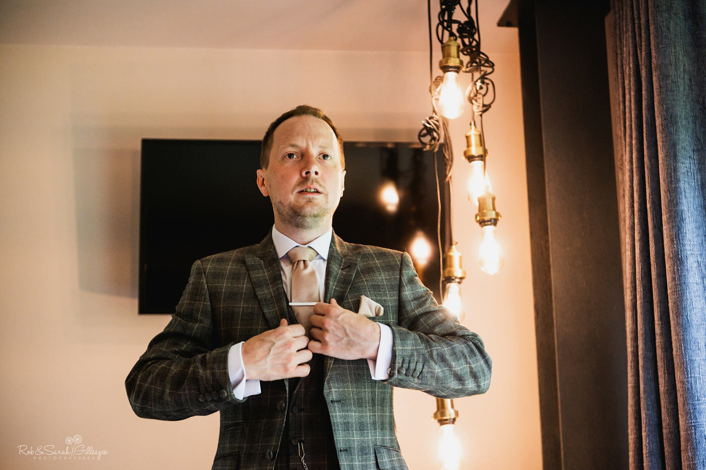 Groom checks tie and jacket as he gets ready for wedding