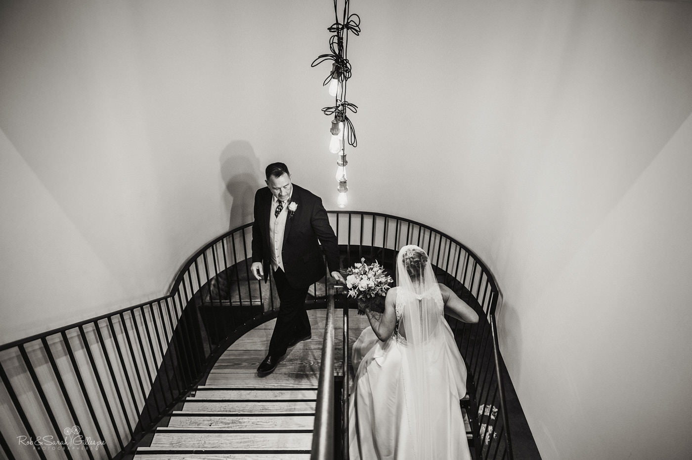 Bride and father on staircase at The Mill Barns wedding venue