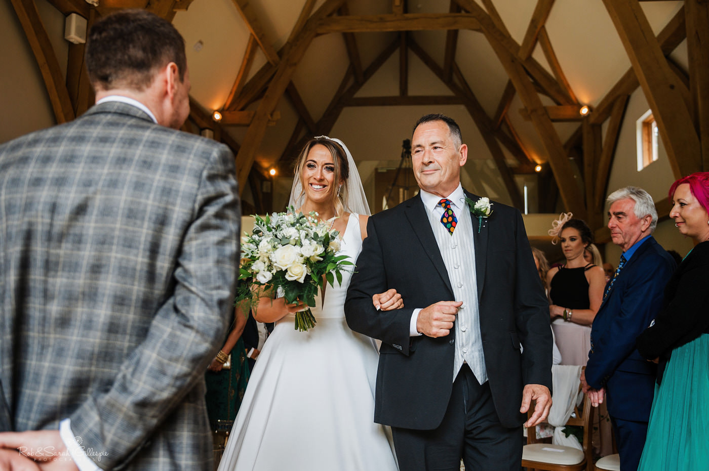 Bride and father enter wedding ceremony. Natural wedding photography at The Mill Barns