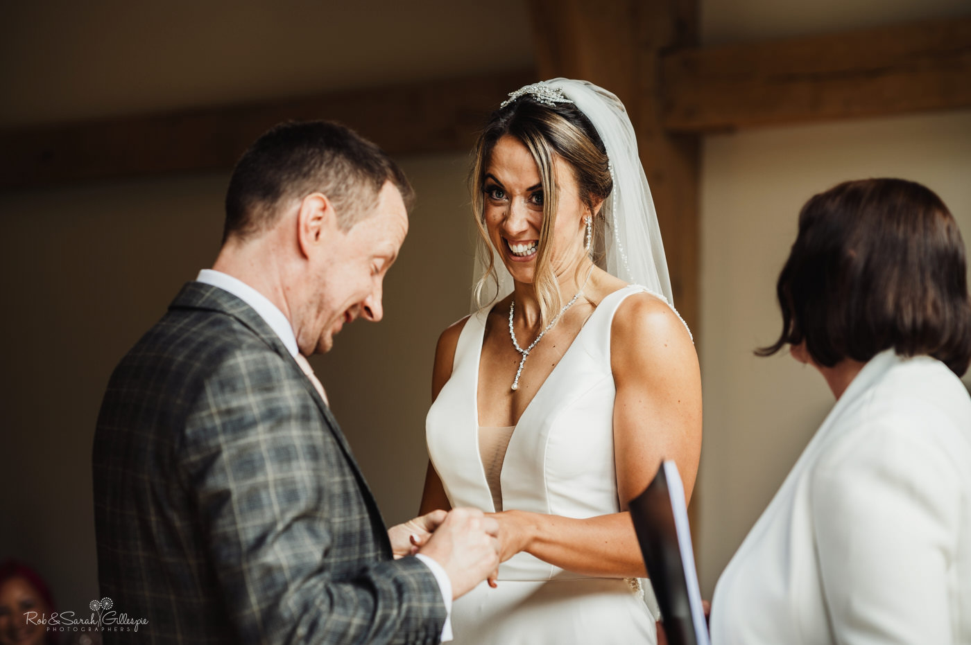 Bride and groom exchange wedding rings as bride pulls funny face at The Mill Barns