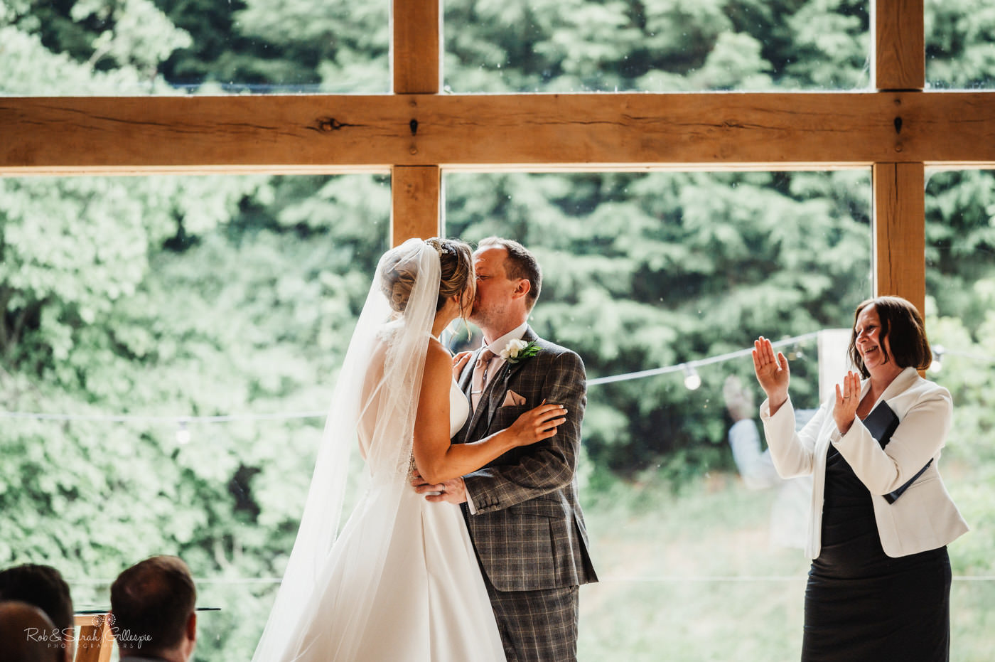Bride and groom first kiss during wedding ceremony at The Mill Barns