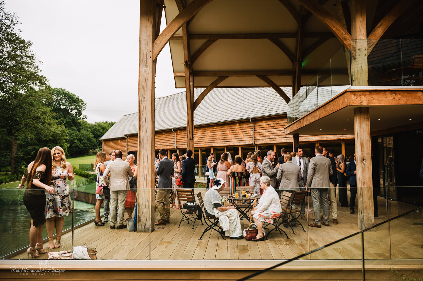 Wedding reception with guests on decking overlooking pond