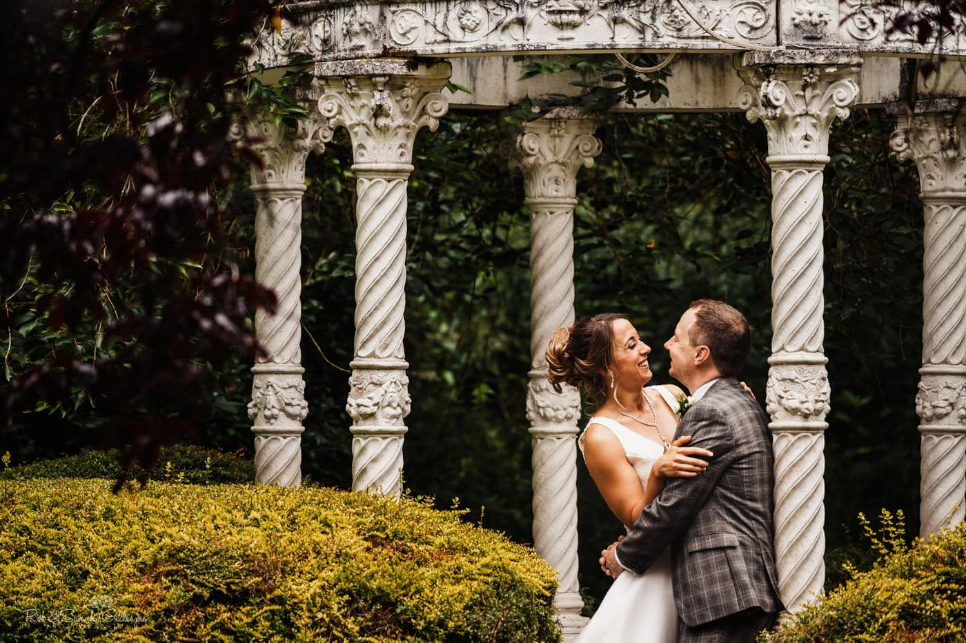 Newly married couple under decorative dome in gardens