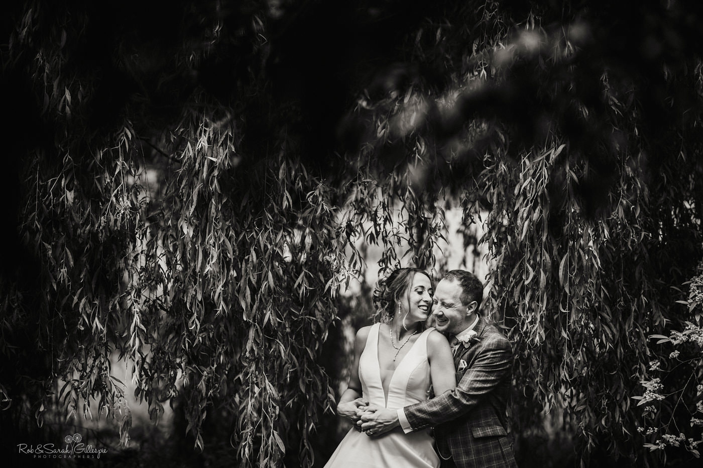 Bride and groom laughing together in gardens
