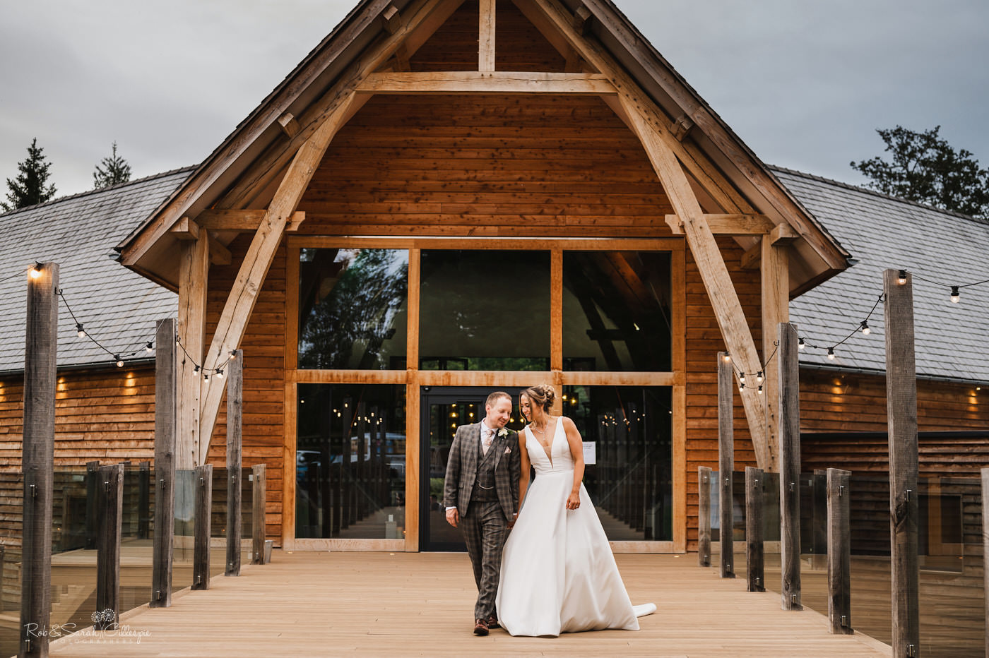 Bride and groom on bridge in gardnes at The Mill Barns