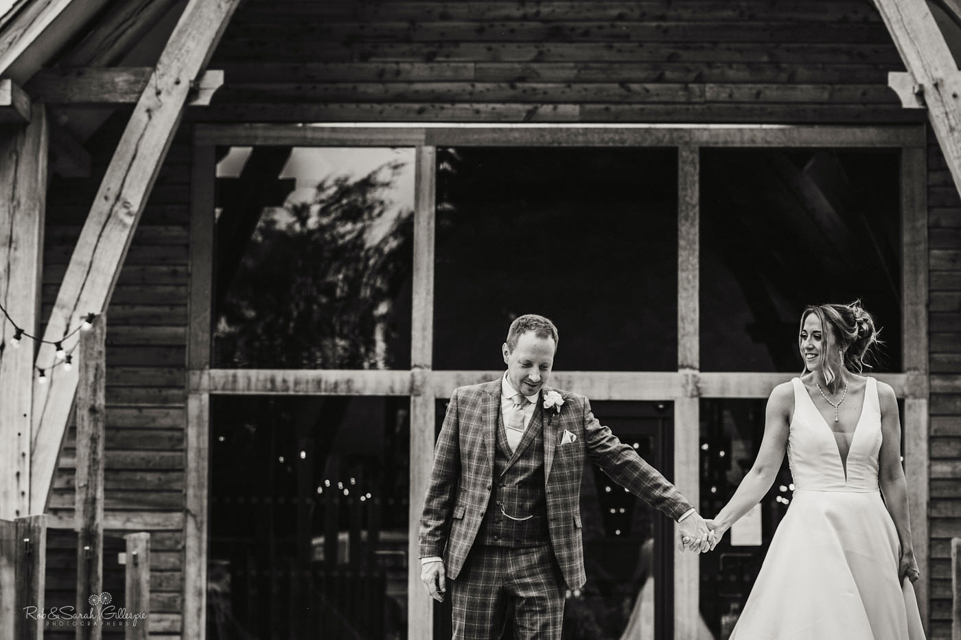 Bride and groom walk together on wooden decking at The Mill Barns