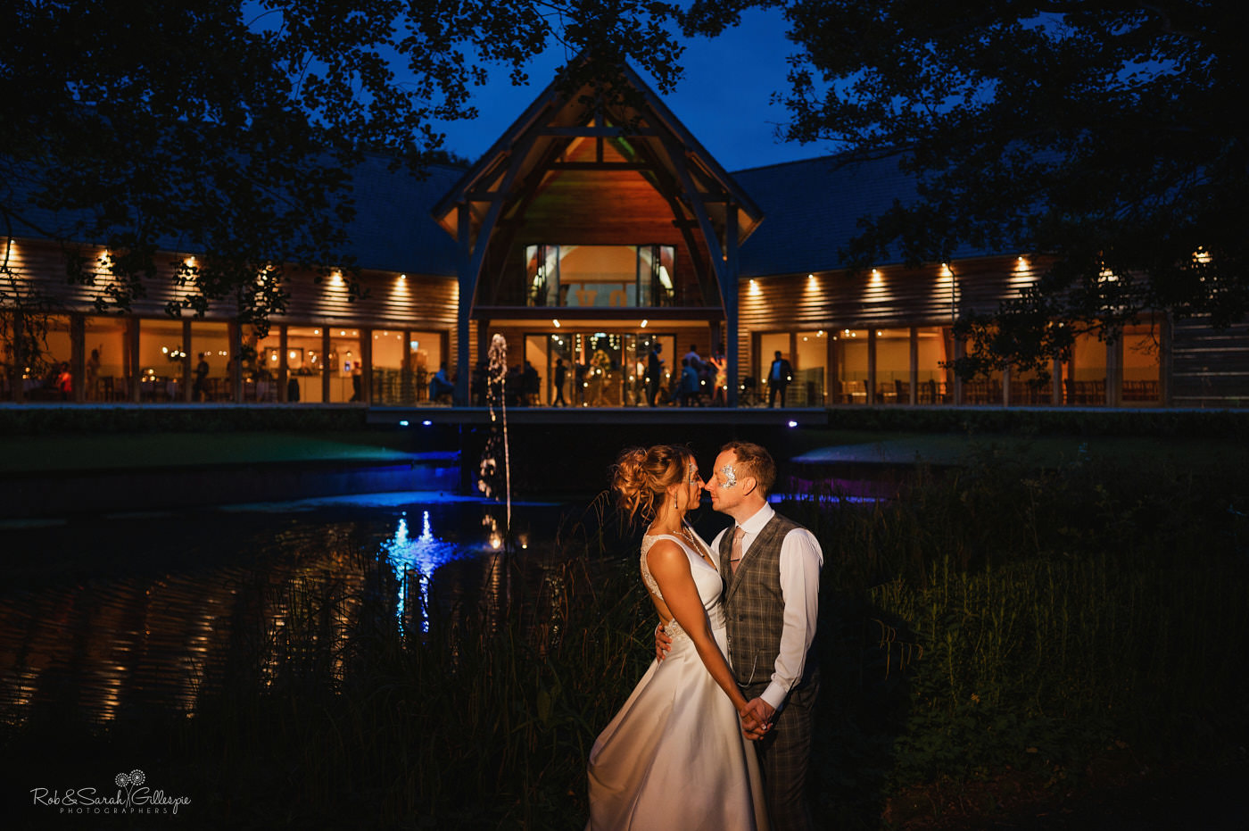 Bride and groom on balcony as guests enjoy evening party. Mill Barns wedding photography