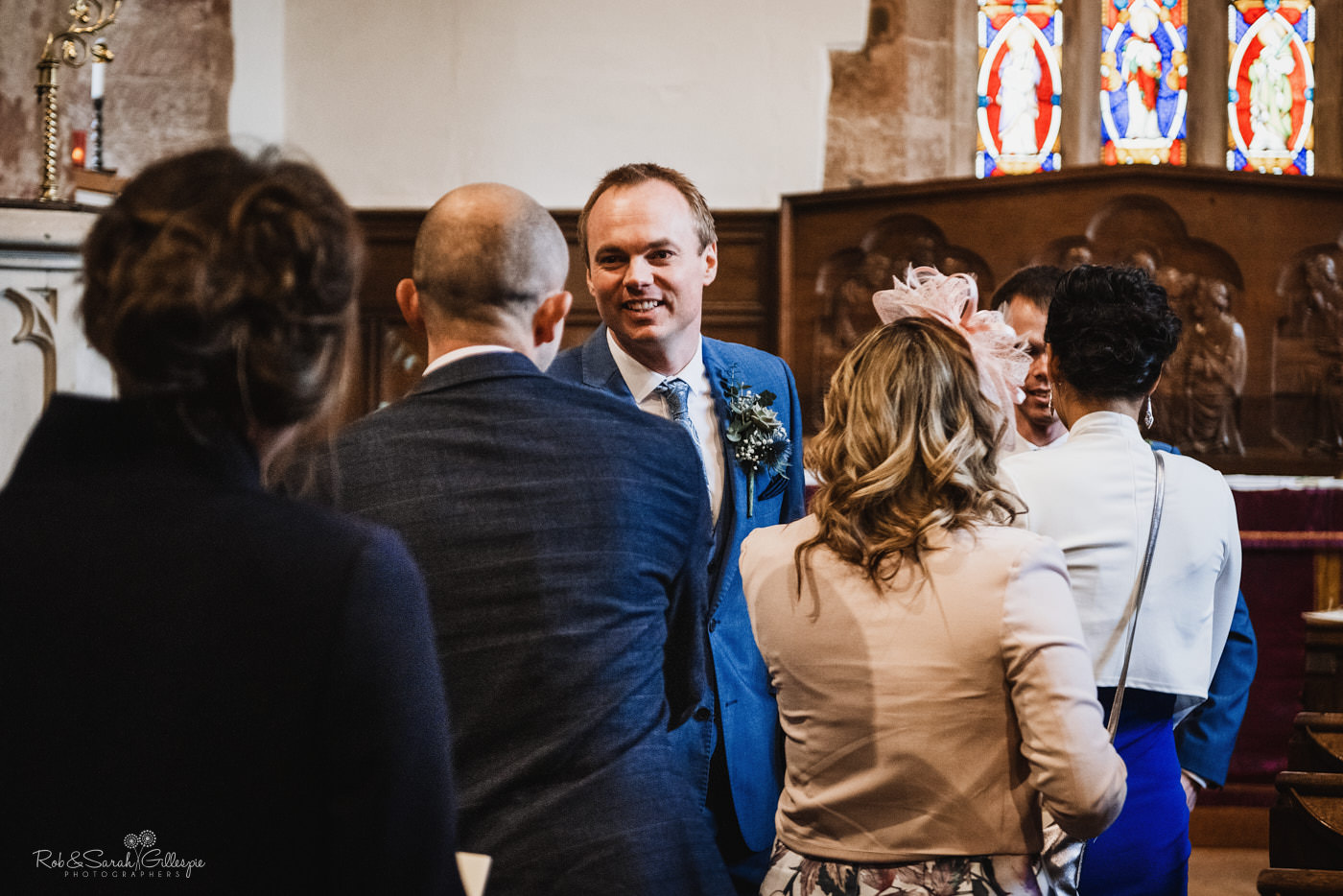Groom greets wedding guests at St Kenelm church in Worcestershire